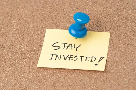 Stay invested, Investment decision idea to stay the course when stock market crisis concept, Thumbtack or pushpin pin to small paper note written Stay invested.