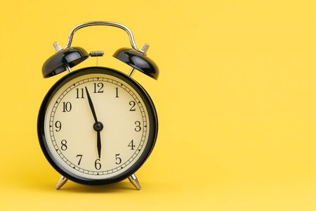 Alarm clock at almost 6 o'clock in the morning on yellow background with copy space using as business reminder, laziness or timer and deadline concept.