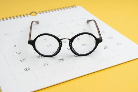 Eyeglasses on white clean calendar on yellow background using as thinking about plan, schedule or meeting apointment concept.