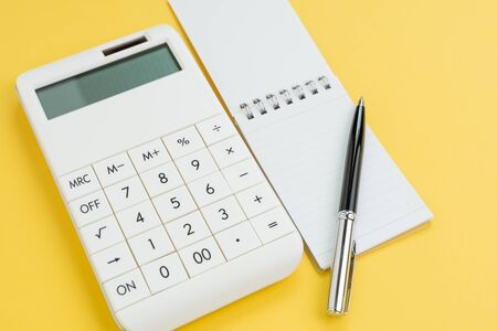 Pen with note paper and calculator on yellow background using as finance, budget planning or financial cost and expense calculation concept.