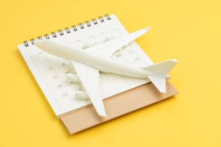Travel schedule, flight plan for vacation or business trip date concept, white commercial toy airplane on clean calendar on yellow background.