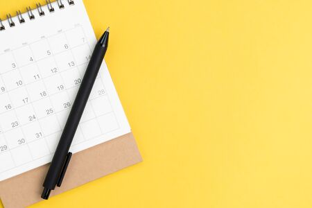 Black pen on desktop calendar in flat lay or top view on yellow background with copy space using as writing plan, circle on important day and event or appointment concept.