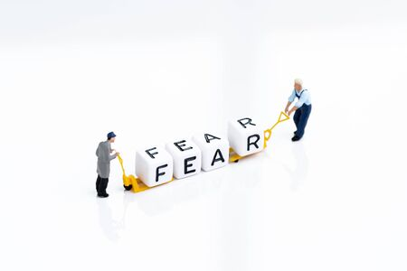 Fear and Greed in investment psychology, panic sell in financial crisis concept, miniature people men pulling forklift with block building the word Fear on white background.