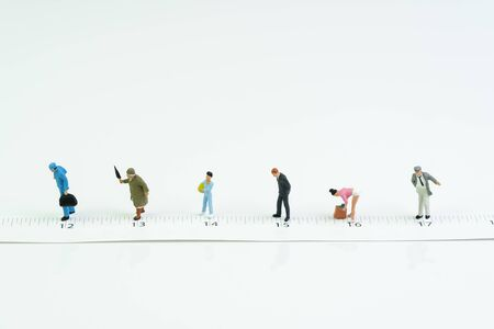 Social distancing, people keep distance in public to protect COVID-19 coronavirus spreading concept, miniature people wait in line keep distance away on measuring tape white background.