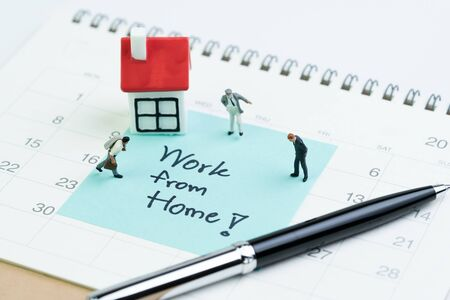 Work from home social distancing in COVID-19 Coronavirus pandemic concept, miniature people businessman office guys standing with house on sticky note written the word Work from home on calendar.
