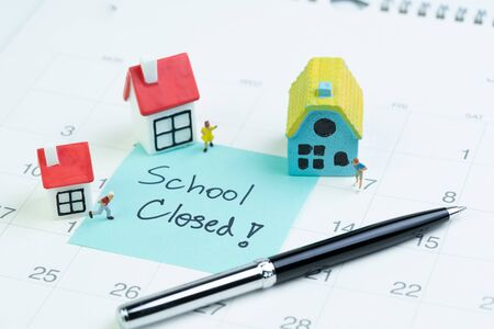 Social distancing school closed to stop and protect from COVID-19 Coronavirus outbreak, miniature kids stay at home, small houses with sticky note on calendar written School Closed.