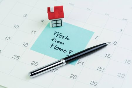 Work from home social distancing in COVID-19 Coronavirus pandemic concept, miniature house on sticky note written the word Work from home on calendar. 免版税图像