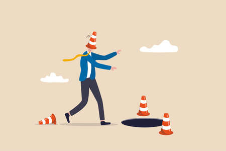 Blind and frustrated business direction, mistake or failure, trap or crisis ahead, risk and uncertainty concept, blindfold businessman cover with pylon walking to fall into the hole or business trap.