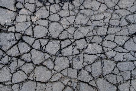 Old worn and cracked asphalt with cracks. Cracked asphalt background 免版税图像