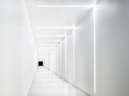 Empty white tunnel with a dark exit at the end. LED strip lighting on the walls.