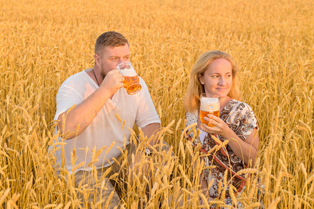 Cheerful man and woman in a wheat field in the rays of the setting sun with pleasure drink beer from glass beer mugs. Awesome vacation mood. Warm summer evening. Archivio Fotografico