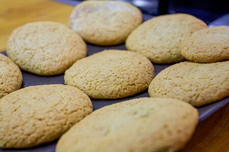 Freshly baked homemade oatmeal cookies freshly baked on a baking sheet on baking paper. Fragrant dessert for tea, cooked with his own hands. 免版税图像
