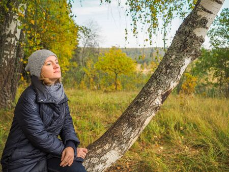 A pensive girl sitting on a birch tree on the outskirts of a withering autumn forest. Cloudy October day.