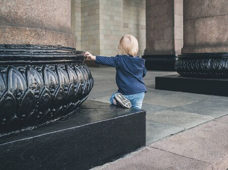 A little girl sits at the base of a massive granite column with her hand resting on her. A monumental building in Moscow built in the mid-20th century.