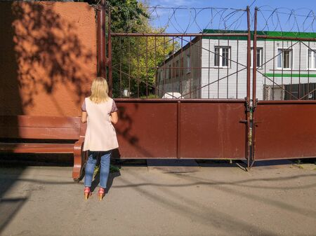 A young girl with blond hair is standing in full growth next to a closed metal gate on a sunny summer day. Protected industrial area. There is barbed wire and a lock on the gate.