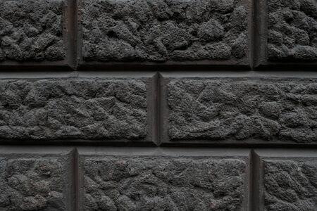 L'elemento a parete è rivestito con stucco che imita i mattoni di pietra di colore nero Archivio Fotografico