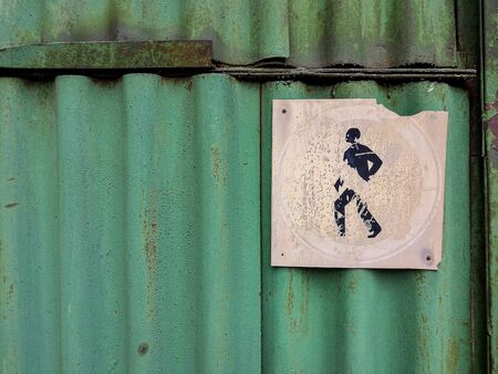 An old faded pedestrian passage ban symbol located on an old rusty green wavy sheet of iron. Grunge style