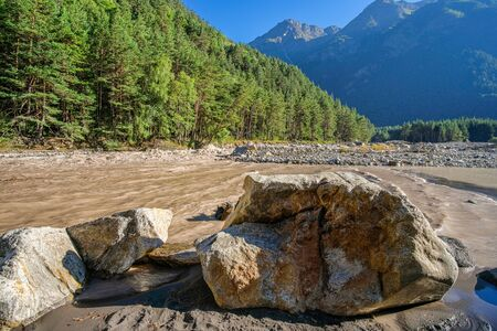 A huge stone boulder against the backdrop of a turbid muddy river in a mountain gorge in the summer. A dense forest grows on the shore.