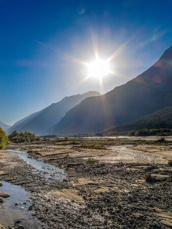The shallowed river in the gorge in the summer against the backdrop of mountains and the shining sun. Turbid water flows along a stony bed.