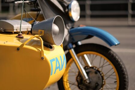 A fragment of a motorcycle of the Russian traffic police of the retro era of the Soviet Union. Text in Russian: State Automobile Inspectorate. A loudspeaker is installed on the wheelchair. Stock Photo