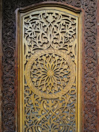Traditional Central Asian floral ornament on an old wooden door.