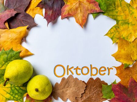 Autumn background with two ripe pears and colorful maple and oak leaves on a white background with the inscription October. Top view with space for your text.