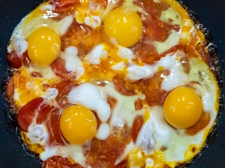 Freshly cooked appetizing fried eggs with red sweet tomatoes in a hot pan. Delicious homemade food. Four yolks of chicken eggs.