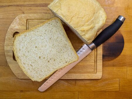Freshly baked homemade bread cut in half on a wooden kitchen board and lying next to a bread knife for cutting bread. Home kitchen.