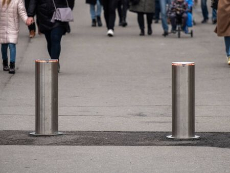 Automatic cylindrical barriers on the pedestrian zone against the background of blurry feet of pedestrians. Фото со стока