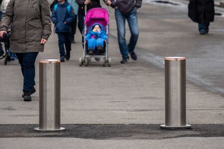 Automatic cylindrical barriers on the pedestrian zone against the background of blurry feet of pedestrians. Car entry prevention. Selective focus.