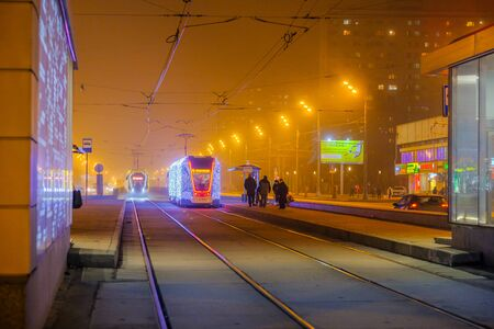 Moscow.Russia. December 26, 2019. Trams in the fog lit by a network of LEDs arrive at a bus stop with passengers. Environmentally friendly public transport, decorated in honor of the New Year holidays Editoriali