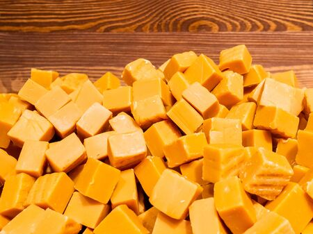 A pile of toffee sweets in orange in the form of cubes. Abstract background of delicious goodies. Imagens