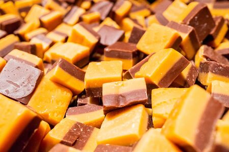 A pile of orange-brown toffee sweets in the form of cubes. Abstract background of delicious goodies.