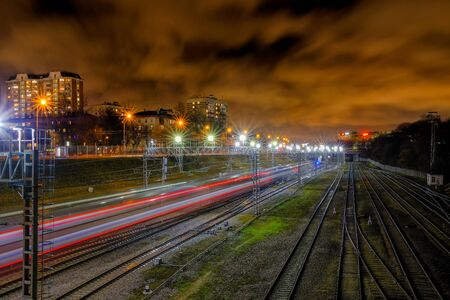 The blurred red line of lights from a train rushing into the distance along the railway tracks at night in the city.