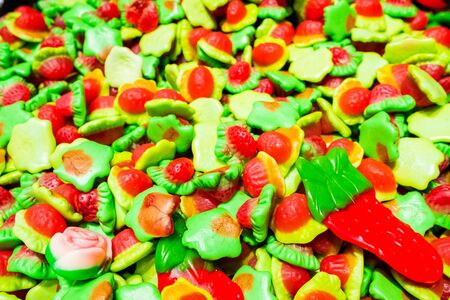 Bright green, yellow, white and red marmalade gummies in the shape of strawberries. Sweet beautiful delicacy made from gel fruit juices. Colorful background. Randomly heaped goodies.