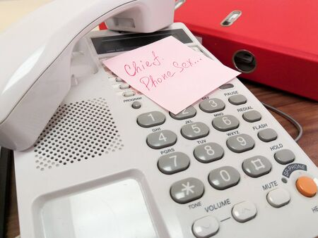 On the keyboard of the landline telephone lies a pink square leaflet with the inscription in red ink Chief, Phone sex. Tired subordinate from tyranny of the authorities.