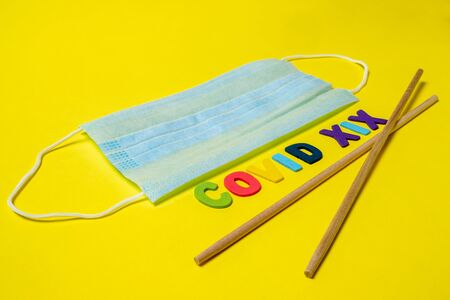 Blue medical mask on a yellow background and Asian chopsticks in the shape of the letter V. The inscription indicates the virus COVID-19. Disease as a treat from Asia. Banque d'images