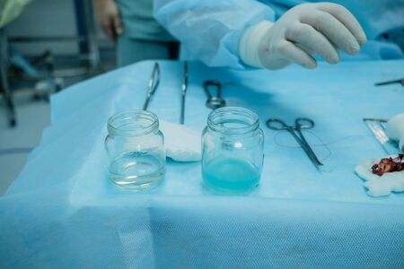 Sterile surgical instruments and glass containers with solutions on the table during a surgical operation. Above the table are the hands of a surgeon in latex gloves.