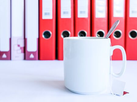 Tea at the office. White ceramic mug with tea on the background of red office folders for documents. Tea from disposable bags. A teaspoon stands in a cup. Tea break at work. Standard-Bild