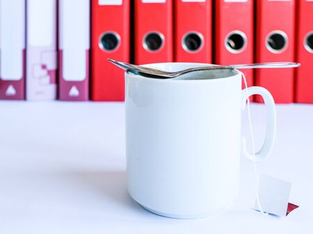 Tea at the office. White ceramic mug with tea on the background of red office folders for documents. Tea from disposable bags. A teaspoon lies on top of the cup. Tea break at work.