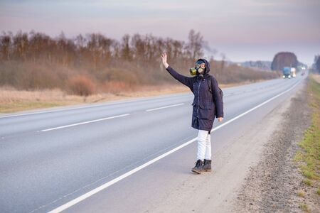 COVID-19. A girl in dark clothes, a gas mask and a hood on her head. Cloudy day in the country. She raises her hand and tries to stop the passing car. Escaping from a zone infected with a coronavirus. Banco de Imagens