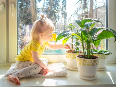 A little blonde baby girl in yellow clothes sits on a windowsill among flowers in pots. The girl smiles and looks with a playful look. The bright spring sun shines through the window.