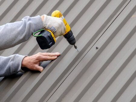 Men's hands in work gloves with a yellow screwdriver screw the roofing sheet to the roof of a country house. Cordless drill. The use of electrical engineering and technology. Archivio Fotografico