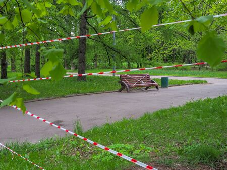 The entrance to the city park is fenced with a signal red and white ribbon during quarantine of the coronavirus pandemic. The park bench is wrapped in a red and white ribbon. Self isolation mode Stock Photo