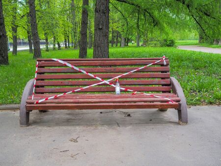 The bench in the city park is wrapped in red and white signaling security tape. On the bench is an empty bottle of vodka. Restrictive measures during quarantine of the coronavirus pandemic.