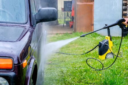 Car wash in the afternoon outdoors with a high-pressure apparatus. A powerful spray with water splashes away the dirt from the purple body of the car, from glass, wheels and tires.