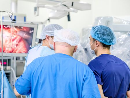 A group of surgeons in a medical uniform oversees medical equipment. The process of performing a surgical operation using a modern robotic surgical system. Reklamní fotografie