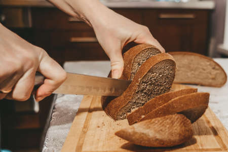 Selective focus on slices of rye bread cut from a loaf with a knife. Archivio Fotografico - 151058480