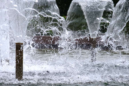 Selective focus on spray of urban fountain and blurred background. A fountain with splashes and drops of water works. Abstract image of a jet of water in a fountain. Frozen motion. Copy space. Reklamní fotografie