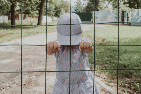 Little baby girl behind bars. The child holds onto the bars of the lattice.